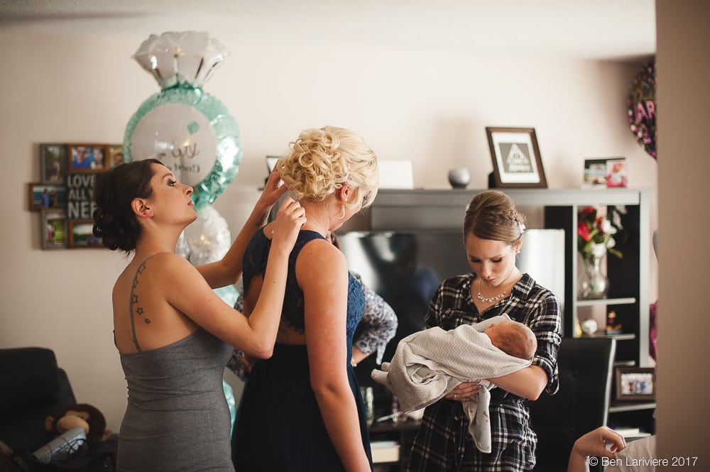 bridesmaids helping with each others hair while bride holds a baby