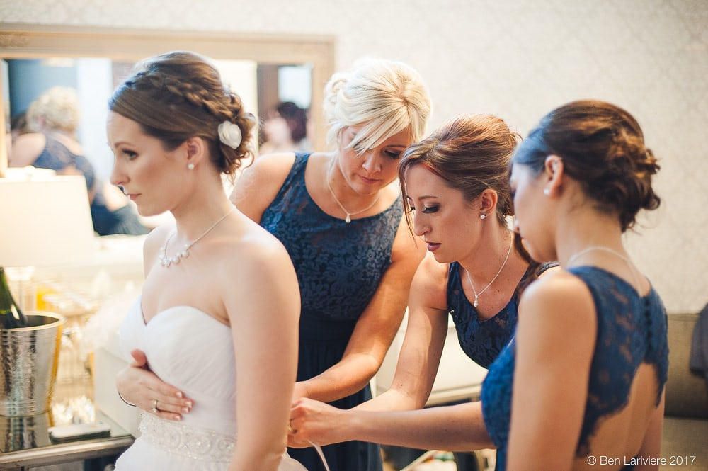 bridesmaids tying up bride's wedding gown