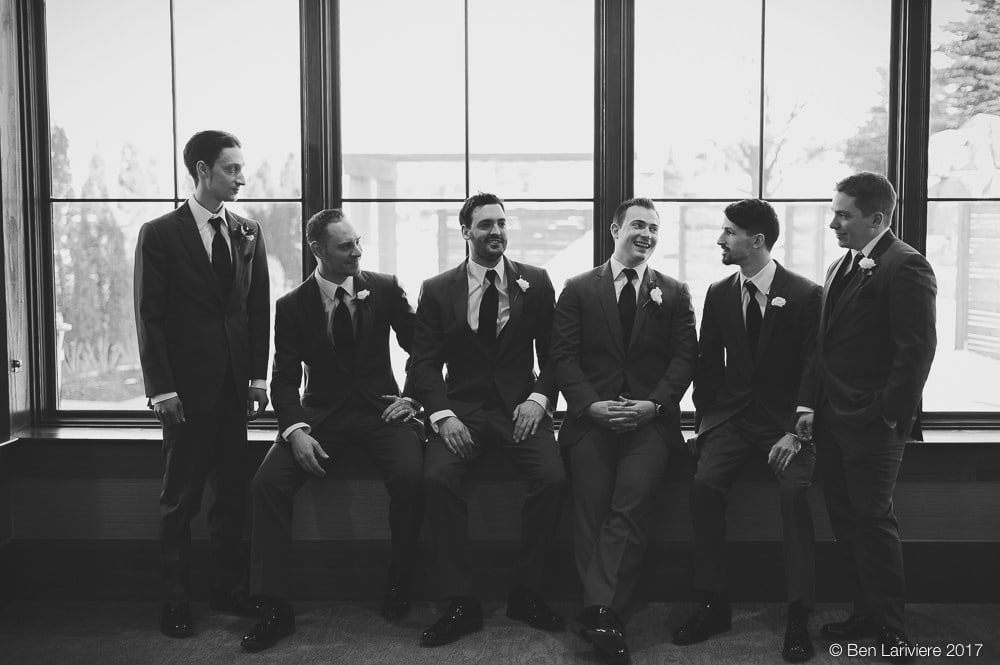 groom and groomsmen sitting by a window