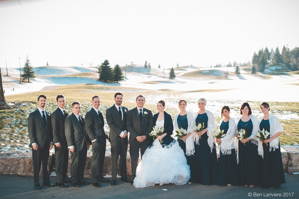 wedding party stand in a line with a snowy golf course in background