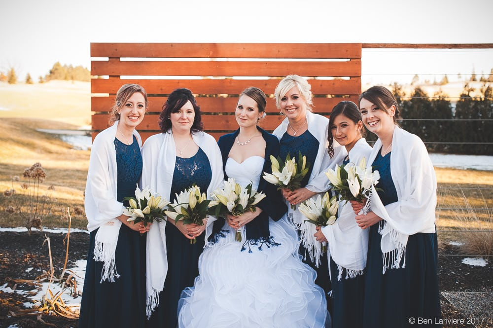 bride and bridesmaids stand in white shawls in front of outdoor wooden wall with golf course in background