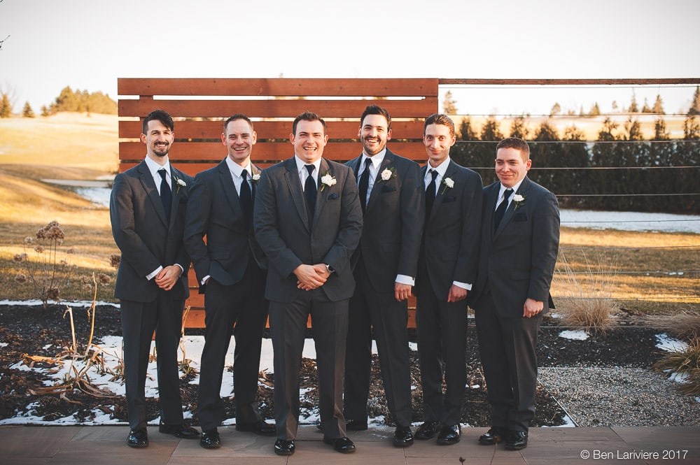 groom and groomsmen laugh standing by outdoor wooden wall with golf course in background