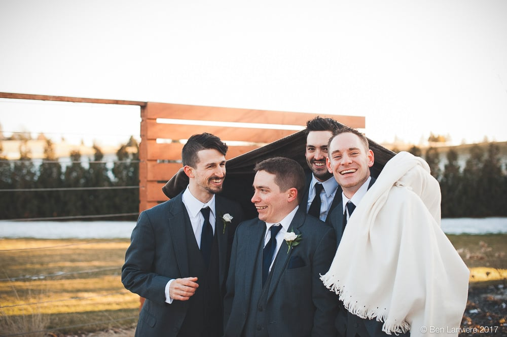 groomsmen huddle under blankets during outdoor winter wedding photos