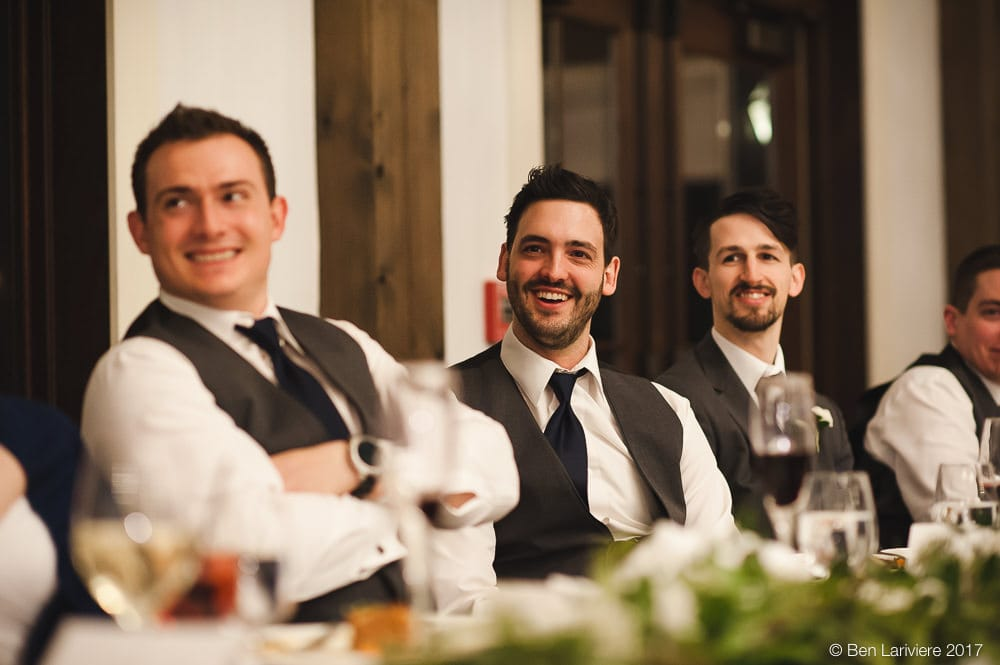groom and groomsmen laugh during wedding speeches