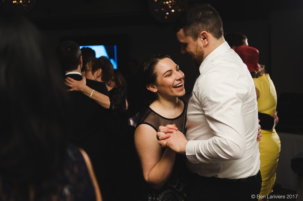 a couple laugh while dancing at wedding reception