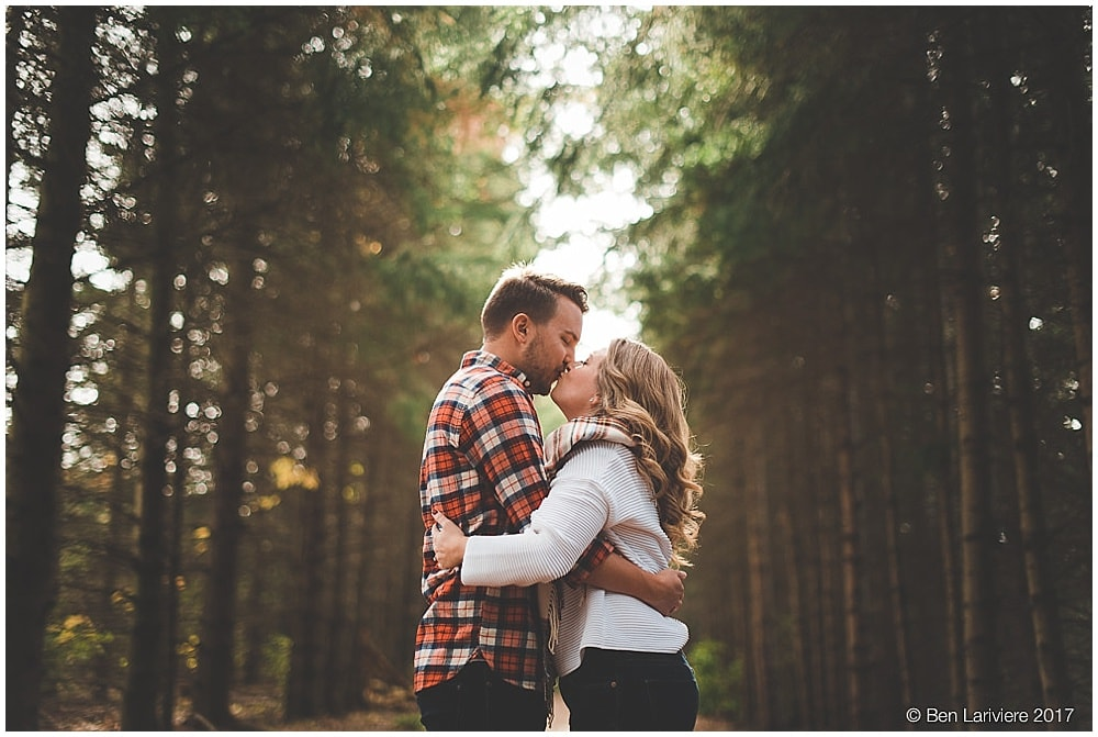 engagement photos of couple kissing surrounded by rows of trees
