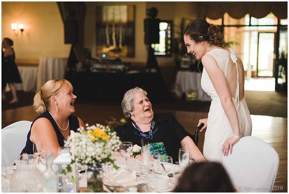 bride laughs with wedding guests at reception