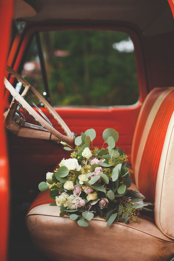 bridal bouquet on seat of red classic vintage pickup truck