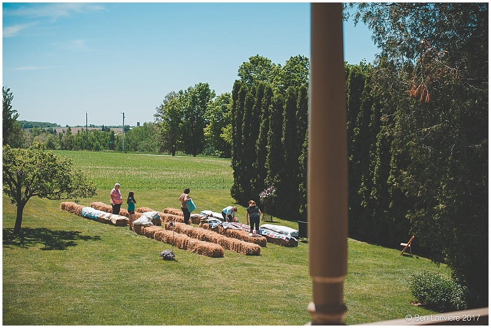 people setting up wedding ceremony with hay bales