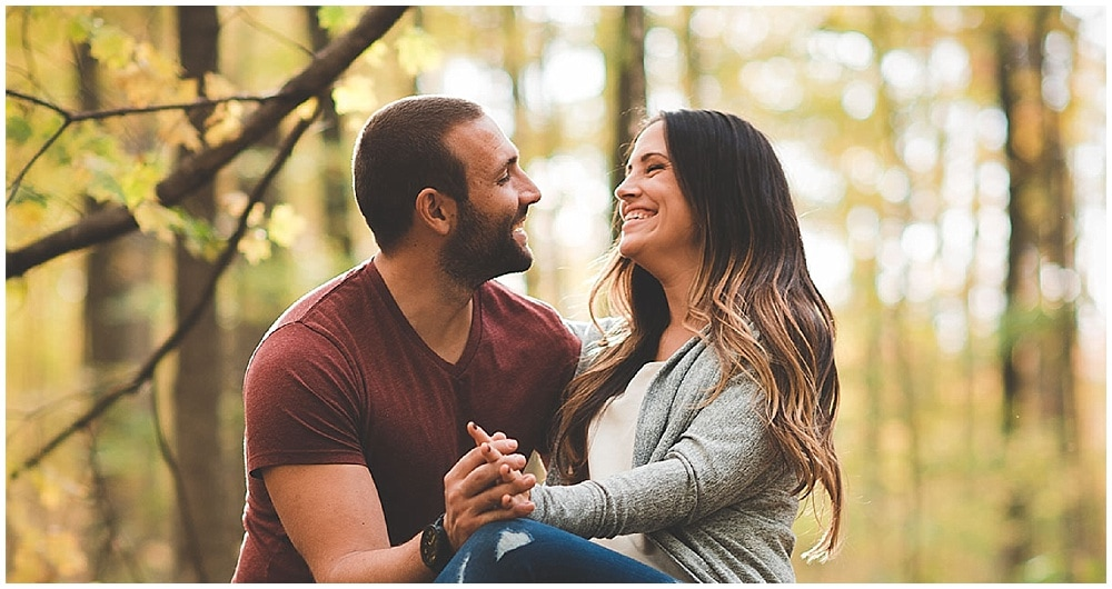 engaged couple laughs surrounded by autumn forest leaves