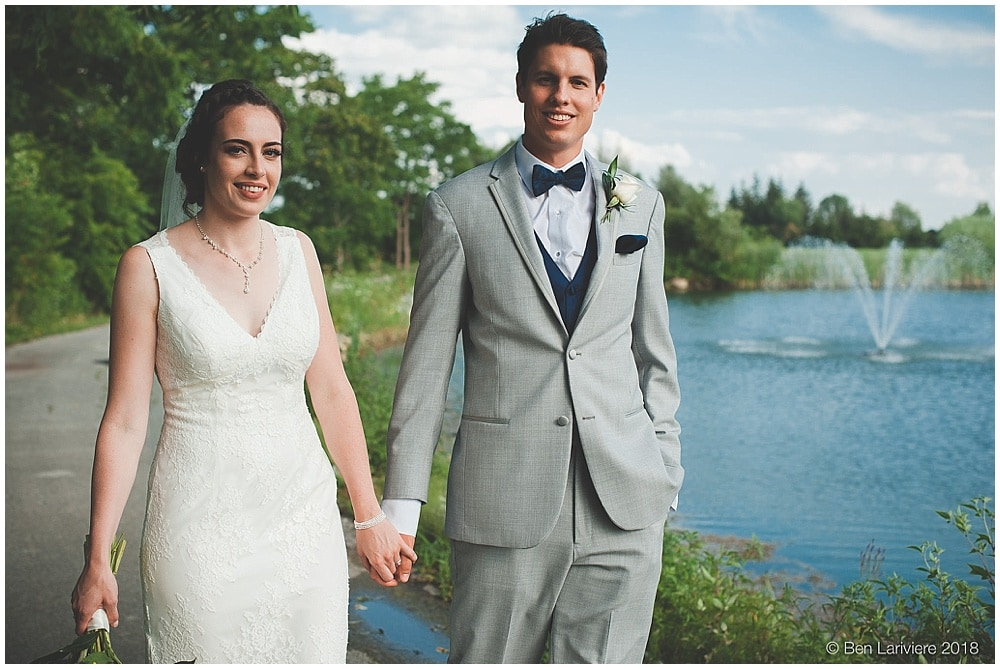 bride and groom walking by pond with fountain