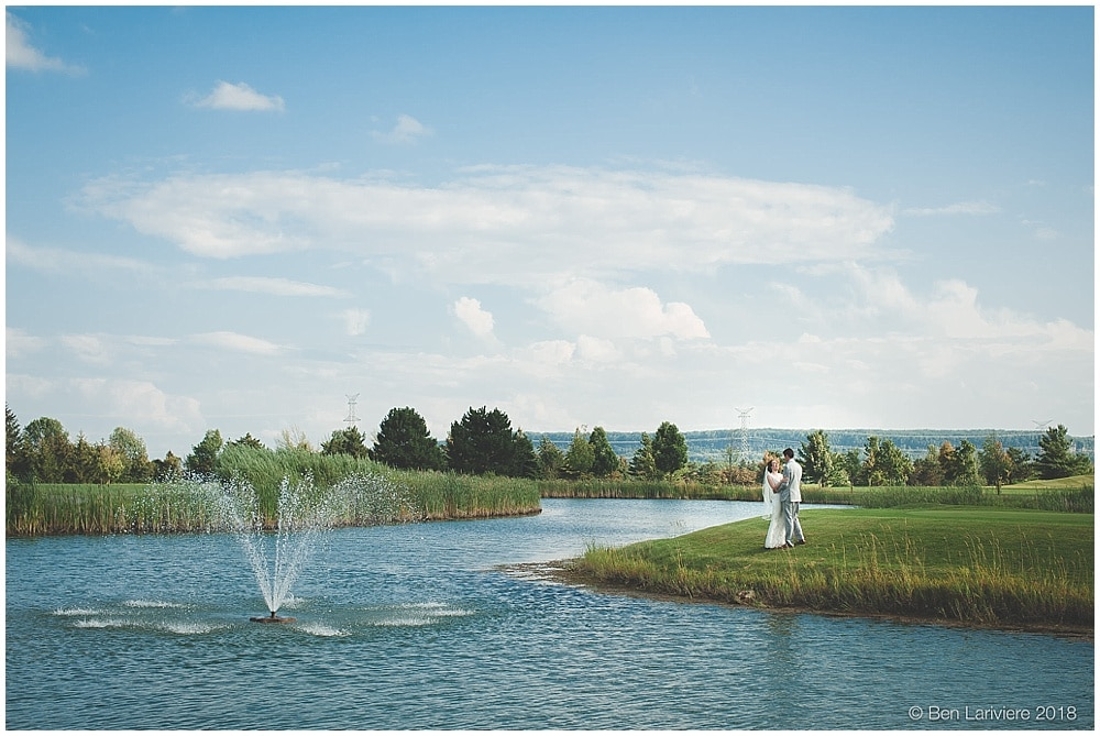 bride and groom stand by pond with fountain