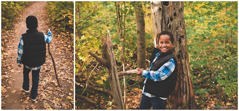 young boy with stick in forest in fall