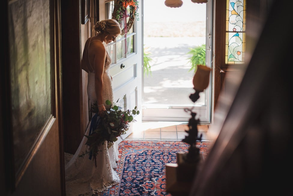 bride stands in shadow by front door of historic house, holding large bridal bouquet