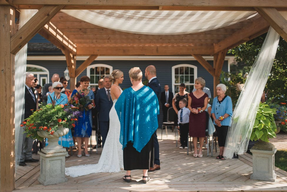 guests stand at start of micro wedding ceremony on backyard deck