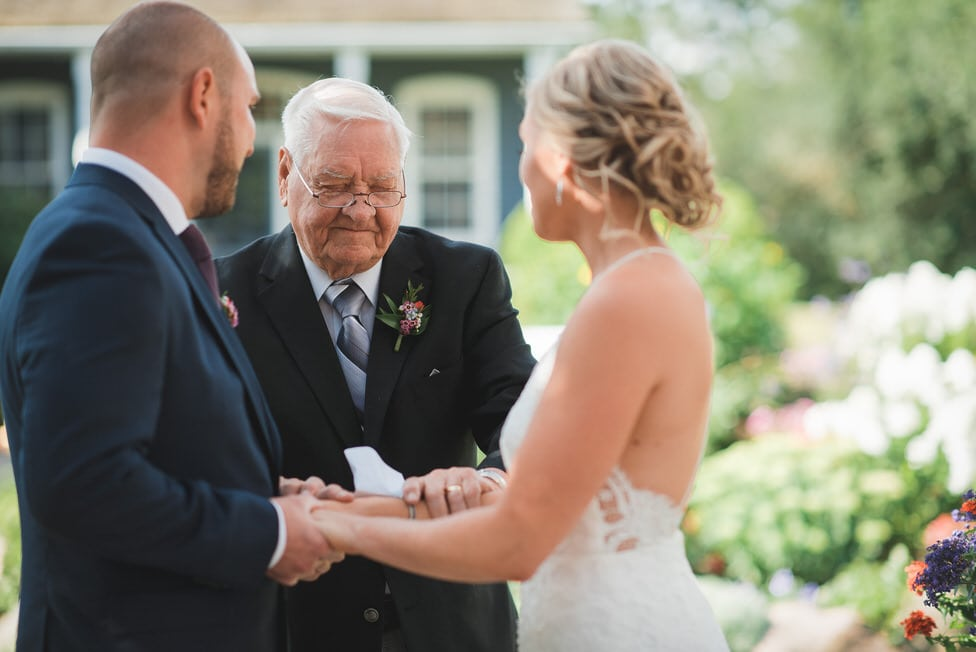 grandfather of bride says a prayer during backyard wedding ceremony