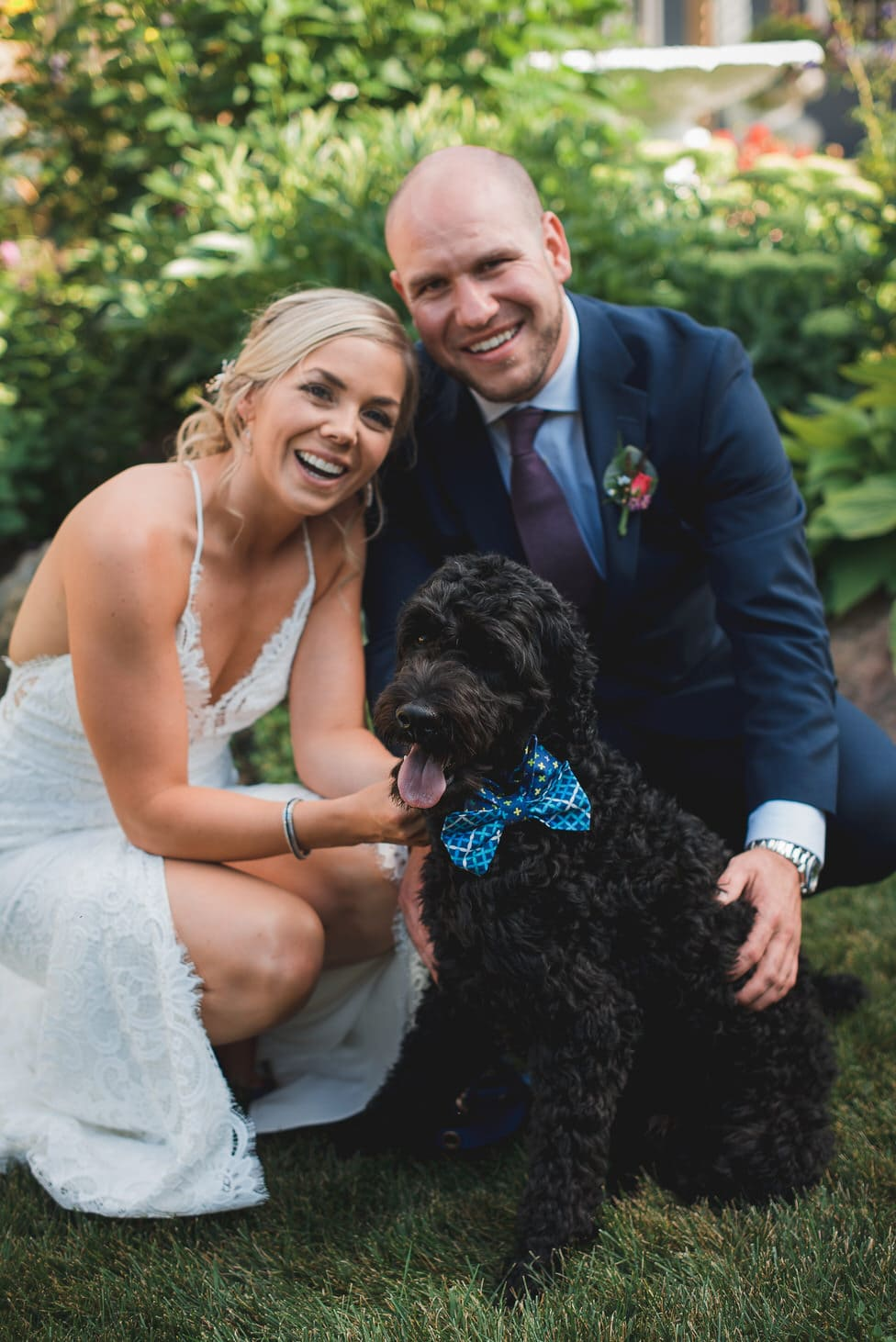 bride and groom pose with their Portuguese water dog in a blue bow tie