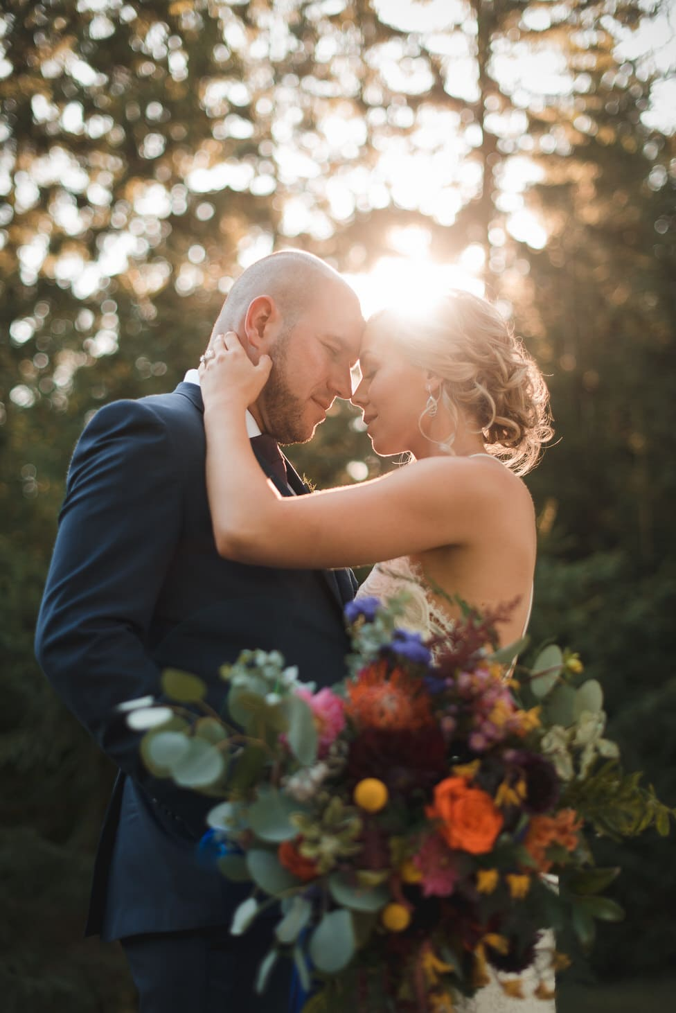 golden hour light shines onto bride and groom in emotional portrait, wedding flowers by designs by cate stratford