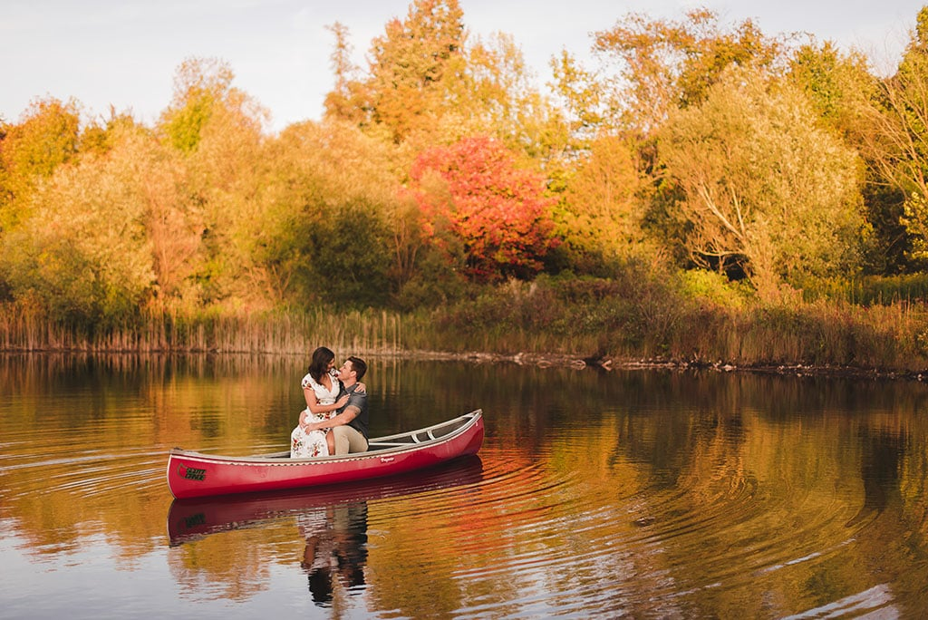 couple kisses in a canoe, floating in a calm pond surrounded by yellow, autumn leaves