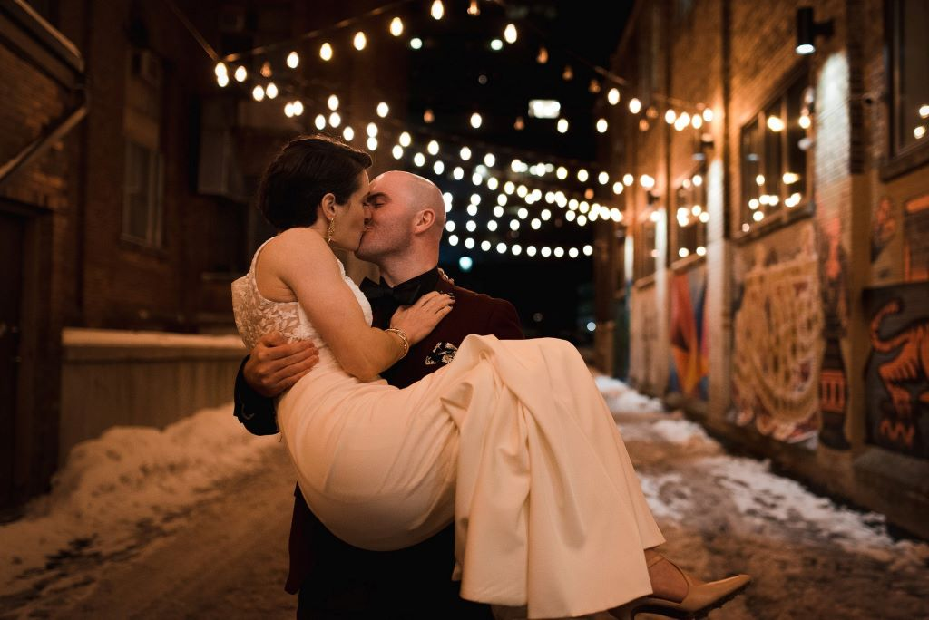 groom carries bride while they kiss at night, Walper Hotel, Kitchener Winter Wedding