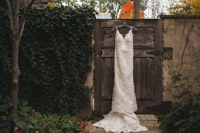bride and groom stand against barn wall