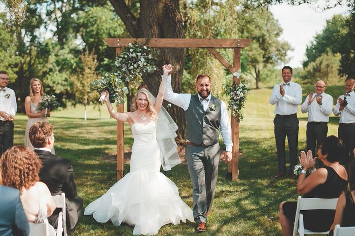 bride mermaid style dress and groom celebrate at outdoor wedding ceremony