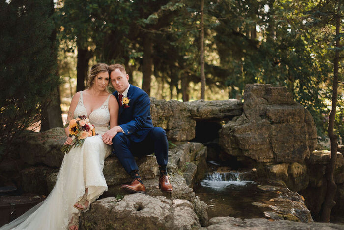 bride and groom sit together by top of waterfall, stratford ontario wedding
