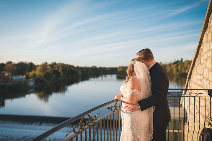 bride and groom look over grand river from Cambridge Mill juliet balcony