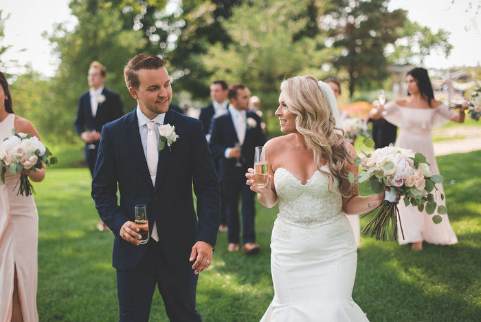 bride and groom look at each other with stemless champagne glasses at stratford country club wedding