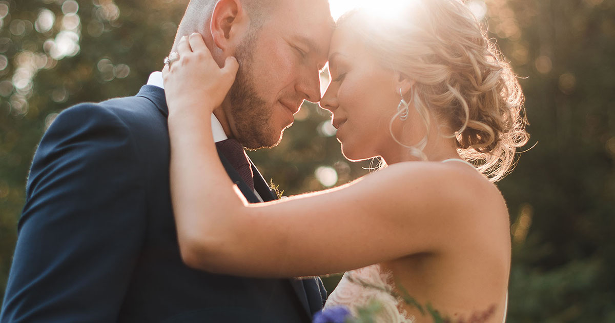 bride and groom kissing in late day sunlight with beautiful bridal bouquet
