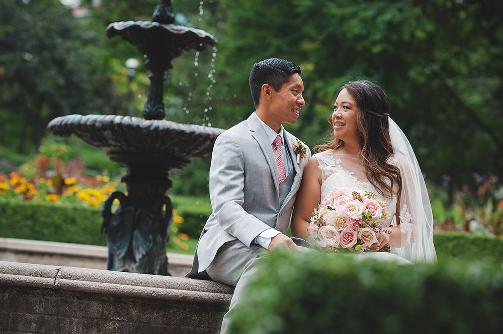 bride and groom sit together by park fountain in toronto