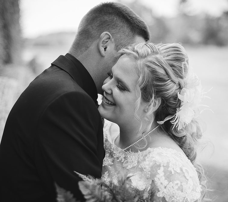 bride and groom laughing by hay bails