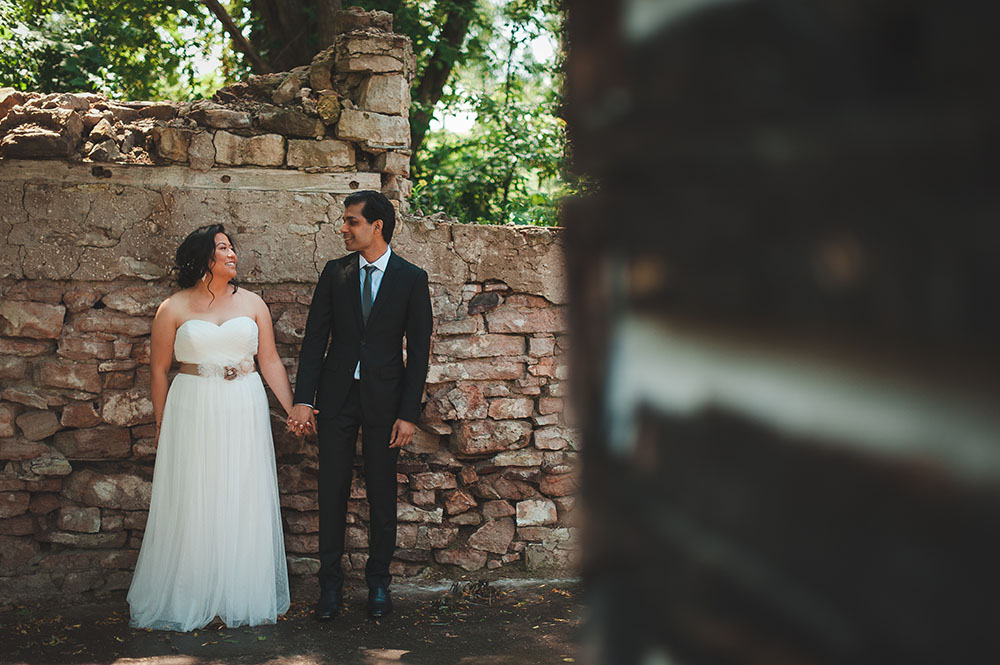 bride and groom stand together hand-in-hand by crumbling barn foundation