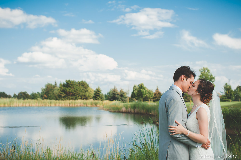 wedding couple kisses by pond and blue sky