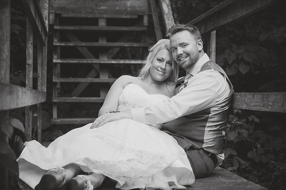 bride and groom smiling and cuddling together on wooden outdoor staircase
