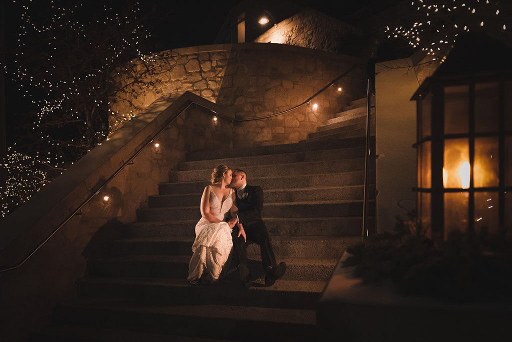 bride & groom sit together at night on steps of Cambridge Mill