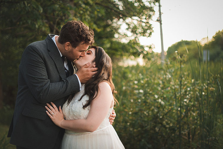 bride and groom kiss surrounded by tall grass