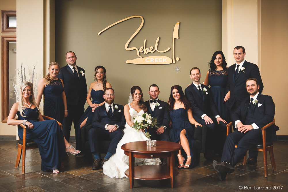 wedding party wearing dark navy arranged on couches and chairs in Rebel Creek Golf Club's foyer