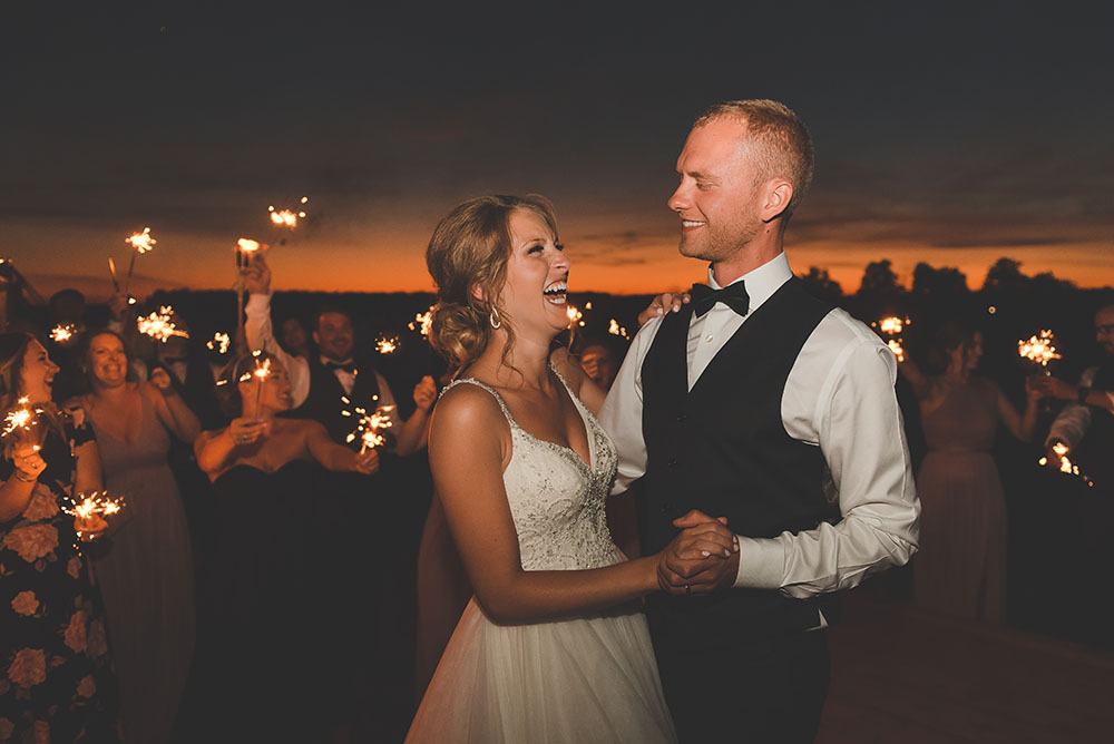 wedding couple dances after sunset surrounded by guests with sparklers